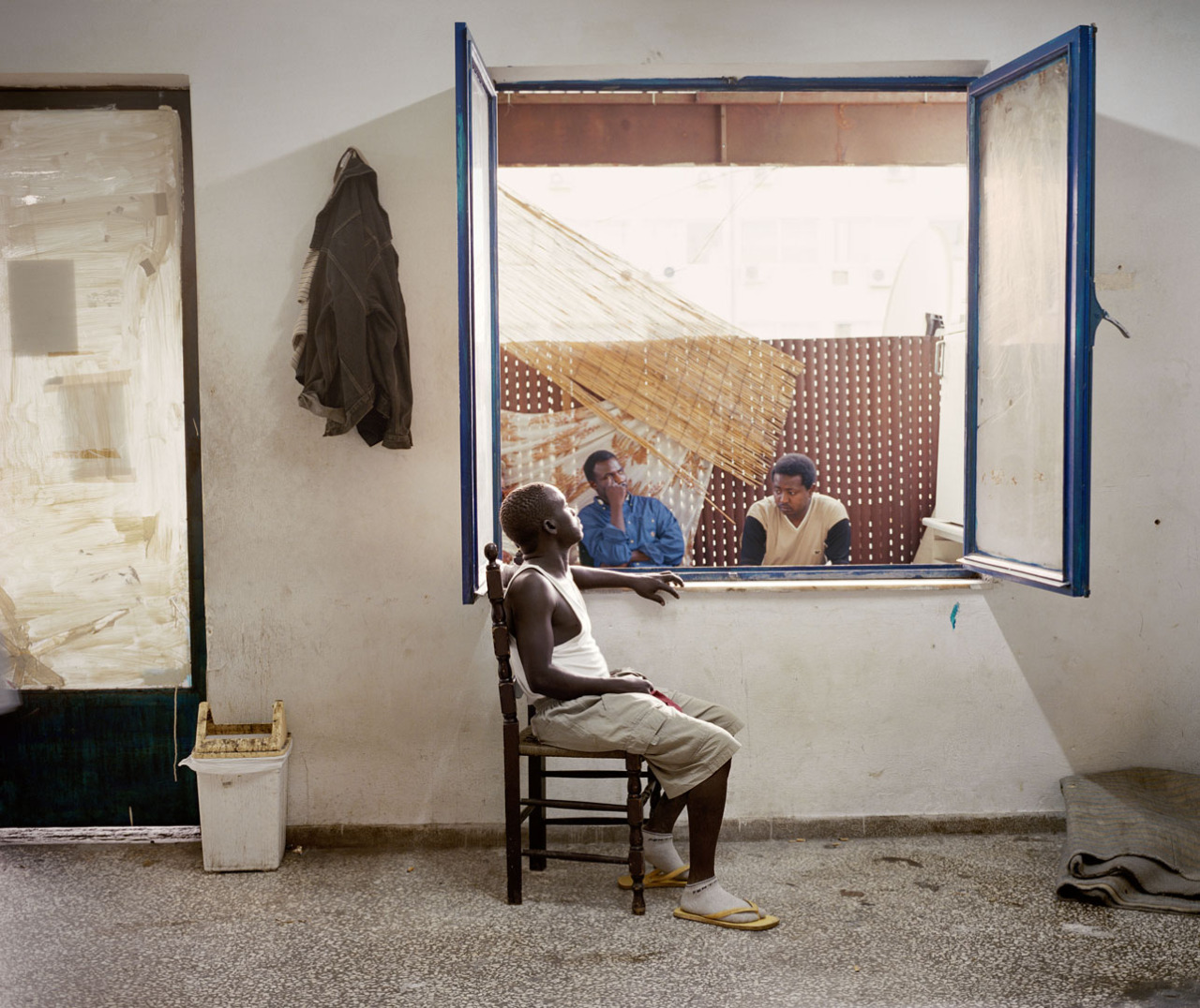 manufactoriel:  Jim Goldberg photographed refugees in Greece who had fled their homelands due to war, disease and/or poverty. Goldberg later travelled to the refugees' countries of origin for the Open See project. He collected the stories of refugees seeking shelter and hoping for a better life. Jim Goldberg and Framing Watching Oprah is the title of a photo of immigrants that Goldberg took in Greece. By intentionally choosing how to frame the photo, Goldberg provides a great deal of information about the immigrants' environment. If he had chosen to take a close-up instead (see right-hand photo), the viewer would have had far less information. Goldberg chose a wide-angle image which allows you to include the immigrants' surroundings in the story you imagine about the photo. Would you have guessed that this photo was taken in Greece? The title Watching Oprah refers to a TV that the men are watching an Oprah Winfrey show on. The TV is outside the picture, so the title is necessary to know what the men are doing. The framing allows us to see certain things in the photo but keeps us from seeing other things. Goldberg lets us see how the men live, for instance, but not specifically what they are doing. In taking your own photo, first think about what you want to show and what you want to leave up to the viewer's imagination. This way you can tell a very special story without giving everything away.