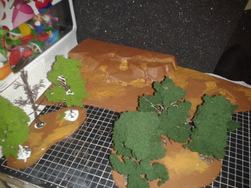 A bunch of Terrain I was working on today, the hill at the back I got real cheap in an auction off ebay so i decided to throw some base colours on it while I worked on my 2 new wooded sections.  I made them using a Foam Core base, and a tree kit I picked up and wanted to try from my local hobby store, the ones on the left are unfortunately fixed to the base which is why I made it a long, almost line of trees so movement in and out isn't a big deal, the ones on the right however pull off their base, so I can pop the trees out when moving units into the woods to make it easier to measure and move, then once the woods are vacated I can pop them back into place.  Tomorrow I'll be flocking the wooded areas and painting the grey of the stones on the hill section.