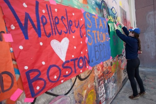 Natalie Griffin '14 hangs signs near the site of Monday's bombings to thank the police and first responders. (via Aftermath of the Boston Marathon attacks)