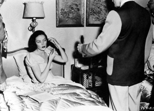 Makeup artist Henry Vilardo holds the mirror for Gene Tierney between shots of Close to My Heart