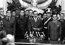 "The sworing-in (March 1976) of General Videla (d. 2013) as president (1976-1981) of Argentina, with the Military Junta around him. 30,000  ""disappeared"" people are his legacy.  El juramento (marzo de 1976) del general Videla (m. 2013) como presidente (1976-1981) de Argentina, rodeado por la Junta Militar. 30.000 ""desaparecidos"" son su legado."