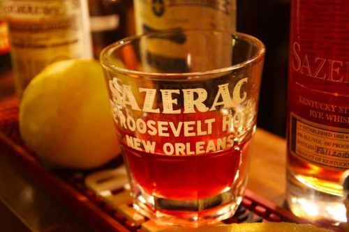 "The predecessor of the Sazerac was a simple brandy toddy, popularized in New Orleans in 1838 by Creole druggist Antoine Amadie Peychaud, who served up the cocktail with his family's bitters. By 1850, the Sazerac cocktail as we now know it was standardized at Merchants Exchange Coffee House (really a saloon) on Exchange Alley, using a few drops of absinthe ""to give it a few more layers of flavor."" The coffeehouse's owner, Sewell Taylor, was also a liquor importer whose most popular product was the Sazerac-du-Forge et Fils cognac which was used in the cocktail. Eventually the name of the coffeehouse changed to Sazerac Coffee House with its most requested drink taking on its name as well. But thanks to the changing tastes of Americans, who preferred American rye to French brandy, the cocktail was most often made with rye whiskey. While you can offend a Manhattan drinker by shaking the spirits-only cocktail, you can wrong the Sazerac lover by committing any of the following sins: make it too sweet, serve it with ice, drop the lemon peel into the drink, or use any bitters other than Peychaud's. (Though adding just a drop of Angostura bitters in addition to the Peychaud's will open up the flavor significantly.)  Sazerac by Chuck Taggart, GumboPages.comGenerous barspoon (roughly one teaspoon) of simple syrup (made with demerara or turbinado sugar at a 2:1 sugar to water ratio) or 1 sugar cube4 big ""slugs"" of Peychaud's bitters (""Slug that bottle from the elbow."")2 ounces rye whiskey2 or 3 dashes of absintheLemon peel1) Start with two Old Fashioned glasses. (No mixing tins!) Chill one in the freezer, and use the other glass to mix the drink while the other is getting frosty. (If you've got a bit more time in between now and when you're drinking, feel free to chill both glasses.)2) Drop in simple syrup and bitters. If using a sugar cube, also drop in no more than a half an ounce of water to help dissolve it.3) Pour in the whiskey and a scoop of ice cubes and stir for 20 to 30 seconds. If the ice is wet, stir for less time. With hard, non-wet ice, do it for 30 seconds. ""You should be able to taste the whiskey. It's a strong drink, so be careful to not over-dilute it [while stirring with the ice].""4) Get the chilled glass and put in 2 or 3 dashes of absinthe. Rotate the glass to evenly coat it with the absinthe. You can choose to toss out the excess or keep it, depending on how much of that anise flavor you want in your cocktail.5) Strain the whiskey from the mixing glass to the chilled glass using a julep strainer.6) Squeeze the lemon peel over the glass and wipe the rim with it, but for god's sake DO NOT drop it in. As Stanley Clisby Arthur, New Orleans author, says in his 1936 book Old New Orleans: A History of the Vieux Carre, Its Ancient and Historical Buildings, ""Do not commit the sacrilege of dropping it into the drink."" Basically you don't want to throw the balance off and let it get too lemony. Also, if you're going to add cognac, Chuck recommends trying half rye and half cognac. If you're going for an all-cognac recipe, use an orange peel instead of lemon.Recommended rye whiskey: Sazerac 6 Year, Rittenhouse, Van Winkle Family Reserve 13 YearRecommended cognac: Pierre Ferrand 1840, Hennessy VSOP, Germain Robin Alambic BrandyHowever, I have to include Las Perlas' Raul Yrastorza who claims to make one of the best Sazeracs around: ""one that is stirred real cold but then poured into a warmed glass where the absinthe rinse was previously lit afire and then extinguished and dumped. I believe that it mimics the warmth of your hand and that warmth opens up the flavor a of the sazerac and orange oils."" [Read on.]"