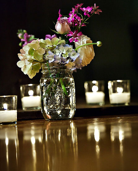 A delicate grouping of garden flowers in a mason jar - hydrangea, ranunculus, spray roses, and asters - a sweet accent for the reception. Image by Susan Stripling Photography