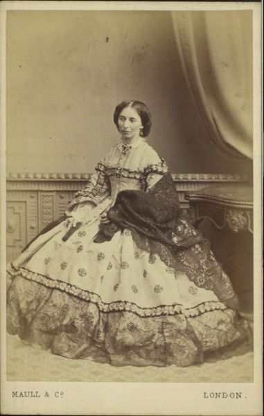 Carte-de-visite photograph by Maull & Co, 1864 London, Manchester Art Gallery  Full length studio portrait of a woman in mourning sitting beside a table. She is wearing a day dress, skirt has an embroidered pattern set at regular intervals, patterned band runs around skirt just below the knee, large lace net hem with scalloped edging, bodice has similar patterned band across the shoulders and bust, upper part of the bodice is quilted with vertical strips, patterned band also runs down the trumpet sleeves, white undersleeves, white lace collar, she has a black lace shawl over one arm. Drawing room backdrop with drape.  EDIT: I don't think this woman is in mourning. Not really sure where that information is coming from.