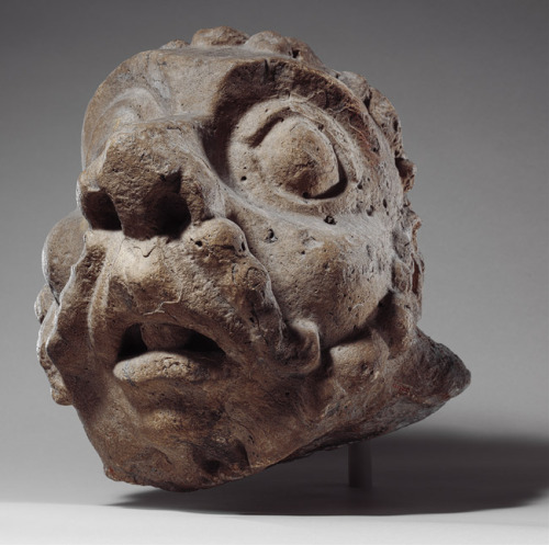 "mediumaevum:  Head of a Grotesque, ca. 1200–1220France, Champagne, Châlons-sur-Marne, Church of Notre-Dame-en-Vaux (?)Limestone The comical effect of the muttonchop whiskers, bulbous nose, enormous eyes, and open mouth of this grotesque head demonstrate the extreme expressions found in marginal sculpture. The head resembles others on corbels supporting the roof cornice of one of the principal churches in Châlons-sur-Marne. The bold features, part of a visual language specific to medieval buildings, are intended to be seen from a distance. Recent research on marginalia suggests that such bizarre heads may have served an apotropaic* function. * intended to ""turn away"" harm or evil"