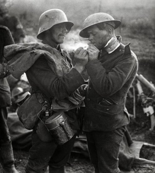 collective-history:  German soldier, giving a cigarette to an English soldier, Christmas Eve, 1914