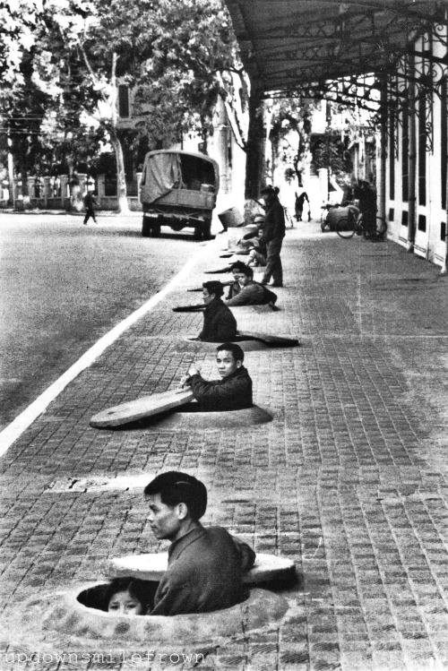 updownsmilefrown:  During an air raid alert, residents of Hanoi wait in chest-deep sidewalk shelters for the all-clear signal. This photo was taken by the first American photographer since 1954 permitted to report on daily life in the capital of North Vietnam, 1967 by Lee Lockwood