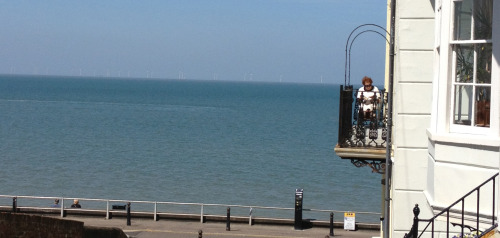 Lady reading on her balcony in Herne Bay in Kent.