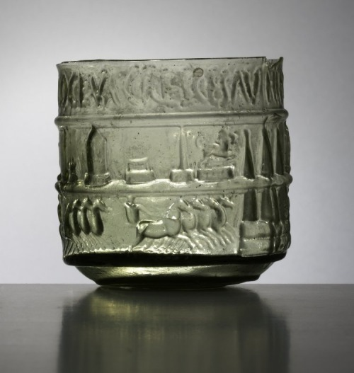 "records-of-fortune:  1st Century Roman. Glass Beaker. Excavated at Colchester, England.  ""Glass vessels with scenes from the circus or the arena may have been intended as souvenirs, showing not only a picture of the sporting event but the names of the participants, who would have been well known to the fans of the games, just as sporting heroes are today. On this beaker the two lower bands of decoration depict the four competing quadrigae (four-horse chariots). The typical architectural features of the race-track, such as the lap-markers, are also shown. The inscribed upper band records [in Latin] that the charioteer Cresces beat his opponents Hierax, Olympaeus and Antilochus. The cup was made by blowing the glass into a mould. This method of manufacture requires careful preparation in making the mould itself, but the actual process of producing the finished vessels is far quicker than making free-blown glass. It is a form of mass-production comparable with the production of terracotta statuettes, lamps and other pottery utensils in moulds."" -British Museum."