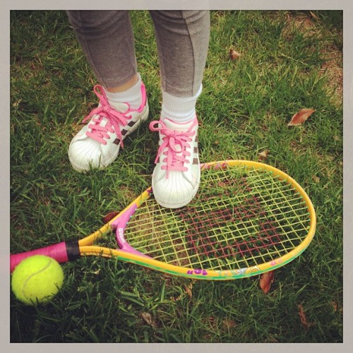 Tiny human tennis racket and shoes.