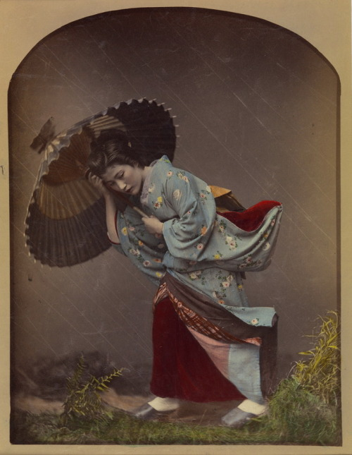 """Woman with Umbrella in Rain"" by Raimund von Stillfried. Artist: Kusakabe Kimbei (Japanese, 1841–1934), 1870s. Commercial photography studios in Meiji-era Japan were renowned for the subtlety and refinement of their coloring techniques. This hand-tinted image of a young woman caught in a heavy rainstorm achieved its naturalistic effect by knitting together multiple strands of artifice: the greenery in the foreground was a studio prop; the flaps of the kimono were suspended by thin wires to create the impression of a strong wind; and long, diagonal marks were made on the negative to suggest streaks of rain. (Photo courtesy of The Metropolitan Museum of Art)"