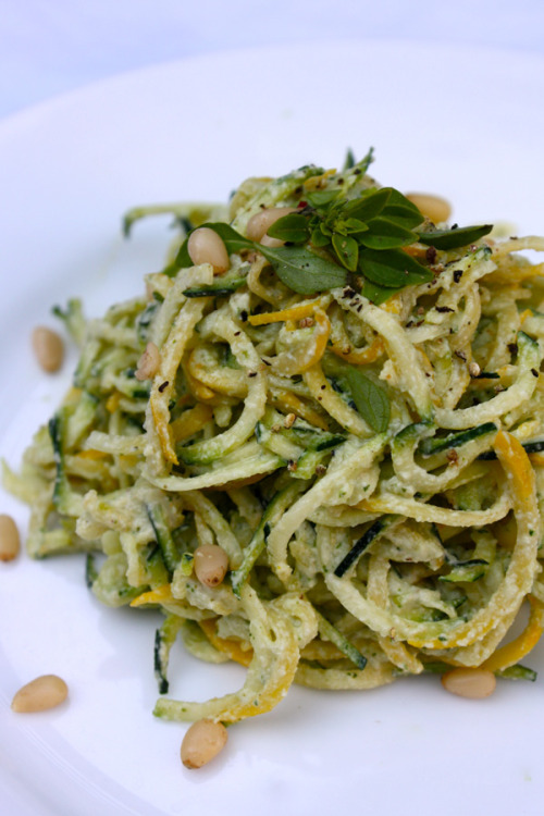 "vegenista:  Raw Squash Noodles with Lemon-Basil Cashew Cream Sauce The farmers' market is abound with so many of my favorite seasonal delights - fresh cherries, asparagus, strawberries, romanesco cauliflower, tomatoes, & summer squash! I've been waiting for the moment that summer squash arrived at my CSA stand & yesterday I caught my first glimpse! Why the excitement? Raw ""pasta"" of course! Last summer I bought a spiral slicer, & made my first batch of zucchini noodles with raw tomato marinara & my life changed that instant! I love pasta, but my ever slowing metabolism doesn't. And really what's pasta without the sauce? Isn't it the topping - a spicy tomato marinara, a creamy cashew alfredo, a zesty basil pesto - where all the flavor is anyway? So the beauty of zucchini noodles is that they are practically, if not totally guilt free! And they're way more fun to prepare than dropping a bunch of dry pasta in boiling water. I enjoy the meditative process of cranking the handle & watching the dense squash become delicate noodles. And I recently cashed in the Joyce Chen for the Benriner, which gives you 3 blade options for varied noodle sizes, & I find the middle size to be perfect for zucchini squash noodles. While I was instantly inspired by the arrival of squash at the market, I was further inspired by the friendly marketeer at my CSA's stand. After a brief hiatus, I am back to my bi-weekly share & anxiously rooted through the contents of my box to see what I had to work with. A bundle of ""basil fino verde"" caught my attention. It certainly smelled like basil, & that was a delight, but looked a bit like thyme. So what should I do with it? Use it as a garnish? Mmmm, sprinkled on pizza, or pasta? Perhaps. I asked the marketeer if he had any suggestions, & boy did he! Win! And turns out he's vegan. Win! Win! He said he had recently used it to make a ""Basil Cashew Pesto"" that he used as a spread on toasted bread, & as a dip for artichokes. Wow. Right? Get me some artichokes & baguette! But then, with zucchini & summer squash in hand, my inspiration bell rang. Ding ding! Raw ""Pasta"" with Basil Cashew Pesto Sauce. I quickly called upon my blog friends for some recipe assistance & came across Dreena's recipe for ""Lemony Cashew Basil Pesto"", & looked no further. What I created was more like a cashew cream sauce than a pesto, & that was certainly the result I was seeking, if you desire more of a ""pesto"" double up on the basil as Dreena did in her recipe.  ""Raw Zucchini Noodles with Lemon-Basil Cashew Cream Sauce"" ***adapted from Plant Powered Kitchen Serves 4 Ingredients: 3 medium zucchini, 3 medium summer squash 3 1/2 Tbsp. freshly squeezed lemon juice 1 clove garlic 3/4 tsp. dry yellow mustard 3/4 tsp. sea salt freshly ground black pepper to taste 4 Tbsp. water, plus more to reach desired consistency  2 Tbsp. extra-virgin olive oil 1 cup raw cashews, soaked over night, rinsed & drained 1 cup basil fino verde leaves  2 Tbsp. pine nuts Preparation: Spiralize the squash & set aside in a colander to drain excess liquid. In a food processor, combine lemon juice, garlic, mustard, salt, pepper, oil, & water, & purée until fairly smooth, scraping down sides of bowl as needed. Add cashews & basil fino verde & purée until smooth & creamy. Add more water to thin out the sauce if desired. Toss zucchini noodles with desired amount of sauce. Top with fresh black pepper, a sprinkle of pine nuts, & basil fino verde leaves.   Tastes like summer around here! While I can imagine that this luxurious topping would be wonderful smothering my favorite brown rice spaghetti noodles, the pairing of crisp raw noodles with the rich & brightly flavored sauce creates a wonderful balance of decandence & freshness. This would also make a wonderful sandwich or cracker spread, if left on the thick side. It would also make a wonderful creamy salad dressing! Yum yum! As I plan on going at least 60% raw this summer, this will become a staple in my raw kitchen! Enjoy!"