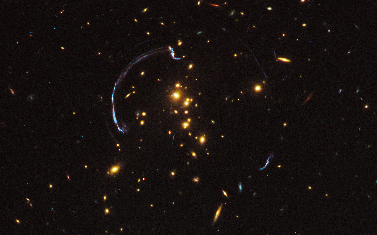 "Day 23 of the 2012 Hubble Space Telescope Advent Calendar, one of 25 photos (eventually).  Thanks to the presence of a natural ""zoom lens"" in space, this is a close-up look at one of the brightest distant ""magnified"" galaxies in the universe known to date. It is one of the most striking examples of gravitational lensing, where the gravitational field of a foreground galaxy bends and amplifies the light of a more distant background galaxy. In this image the light from a distant galaxy, nearly 10 billion light-years away, has been warped into a nearly 90-degree arc of light in the galaxy cluster RCS2 032727-132623. The galaxy cluster lies 5 billion light-years away. The background galaxy's image is not only stretched by the lensing, but split into multiple apparent images, across the upper left and at lower right. (NASA, ESA, J. Rigby, and K. Sharon, M. Gladders, and E. Wuyts, University of Chicago)"