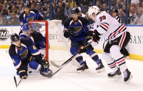 Blues defenseman Kris Russell (4) tries to block a shot by Chicago forward Jimmy Hayes (39) in second period action during a game between the St. Louis Blues and the Chicago Blackhawks on Saturday, April 27, 2013, at the Scottrade Center in St. Louis. Also defending on the play are Blues goaltender Brian Elliott and forward Adam Cracknell (79). Photo by Chris Lee