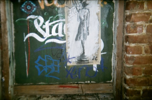 "draw-on-walls:  This is a picture taken with my holga 135 of my first wheat pasting on the street. It is at North Shore in Chattanooga, TN. My paste mix was actually mostly elmers glue mixed with a tacky glue. Then I went back over it with a real Wheat Paste. It has been up and safe for almost two months. I pasted it up december 2012. My process is that I take a piece of newspaper. Put white gesso or wallpaper paint on it. Then I paint with black India Ink. I try and draw images I find elegant or that relate to me or tell a story. This particular image is a woman in the rain and I find great elegance and peace within the image. I like to paste my art in public so that someone walking by can experience a moment of artistic enjoyment or an emotional reaction in a place that they didn't expect to. I put my initials on this piece in the bottom right corner. After this I put my nickname ""Jack"" and the date on the painting."