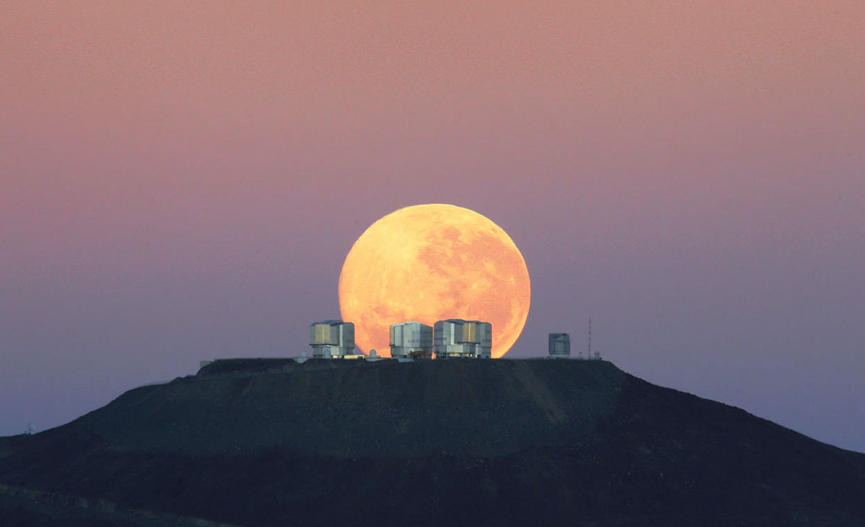 From The European Southern Observatory, one of 34 photos. As the full Moon sets, the Sun is about to rise on the opposite horizon. The ESO's Very Large telescope (VLT) has already closed its eyes after a long night of observations, and telescope operators and astronomers sleep while technicians, engineers and day astronomers wake up for a new day of work. Operations never stop at the most productive astronomical ground-based observatory in the world. ESO staff member Gordon Gillet welcomed the new day by capturing this stunning image from 14 km away, on the road to the nearby Cerro Armazones. (ESO/Gordon Gillet)