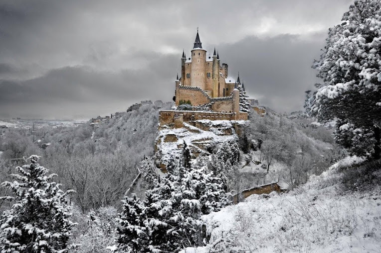 The Alcázar of Segovia is a stone fortification, located in the old city of Segovia, Spain. Rising out on a rocky crag above the confluence of the rivers Eresma and Clamores near the Guadarrama mountains, it is one of the most distinctive castle-palaces in Spain by virtue of its shape – like the bow of a ship. The Alcázar was originally built as a fortress but has served as a royal palace, a state prison, a Royal Artillery College and a military academy since then. The castle is one of the inspirations for Walt Disney's Cinderella Castle. The Alcázar of Segovia, like many fortifications in Spain , started off as an Arab fort, which itself was built on a Roman fort but little of that structure remains. The first reference to this particular Alcázar was in 1120, around 32 years after the city of Segovia returned to Christian hands (during the time when Alfonso VI of León and Castile reconquered lands to the south of the Dueroriver down to Toledo and beyond). However, archaeological evidence suggests that the site of this Alcázar was once used in Roman times as a fortification. The shape and form of the Alcázar was not known until the reign of King Alfonso VIII (1155–1214), however early documentation mentioned a wooden stockade fence. It can be concluded that prior to Alfonso VIII's reign, it was no more than a wooden fort built over the old Roman foundations. Alfonso VIII and his wife, Eleanor of Plantagenet made this Alcázar their principal residence and much work was carried out to erect the beginnings of the stone fortification we see today. The Alcázar, throughout the Middle Ages, remained one of the favorite residences of the monarchs of the Kingdom of Castile and a key fortress in the defense of the kingdom. It was during this period a majority of the current building was constructed and the palace was extended on a large scale by the monarchs of the Trastámara dynasty. In 1479 Isabel I was crowned Queen of Castile at St. Michael's Church in Segovia as she was staying at the Alcázar..