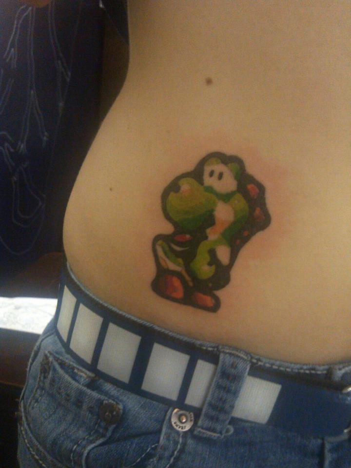 fuckyeahtattoos:  This is (what I think) is a cool pixelated version of Yoshi, a character from Nintendo. I love it because it looks like a sticker (that just so happens to be permanent) This was done by Courtney Pownall at Heart and Soul Creations in Sheridan, Oregon.   Follow me if you would like, vicious-koala.tumblr.com. I'm always getting more tattoos.