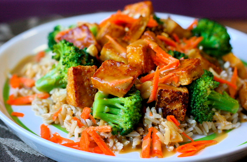 Soy-Mirin Tofu Over Rice with Broccoli and Peanut Sauce Serves Two 1 Block Extra Firm Tofu, pressed, cut into small squares1 tbs Canola or Peanut Oil2 tsp Soy Sauce2 tsp MirinBroccoli, steamed1 Carrot, peeled and shreddedPeanuts, crushed (optional)1 Cup Dry Brown Rice Peanut Dressing1/4 Cup Peanut Butter1/4 Cup Water (or coconut milk if you have it!)1 Tbs Sugar1 Tbs Soy Sauce1 Tbs Seasoned Rice Vinegar1 tsp Hot Chili Oil1 Pinch Salt Start cooking your rice. Mix sauce ingredients until smooth (be patient, it'll look like hell at first) and set aside. Pan fry tofu in the oil over high heat in a non-stick skillet until browned on both sides. Drain and return to hot pan (turn off the heat). Mix soy sauce and mirin together and pour over tofu, mixing well. It will bubble up and form a light glaze. Plate rice, add broccoli, tofu, carrot, and crushed peanuts. Drizzle with sauce and serve.