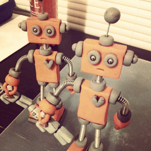Work-in-progress: The robots have began cloning themselves! on Flickr.Finishing two Orange Olie commissions, with light rustic finish. MY 3 ROBOT LAWS: 1: Each Robot is unique, one of a kind. 2: NOT intended for children, NOT Bendable, for display only. 3: Not intended for those that do not think robots are awesome. HOW THE ROBOTS ARE MADE: Each robot is handmade by me. Polymer clay is shaped into robotic goodness, beads added for eyes and wire woven into springs that make the neck, arms & legs (coiling gizmo rocks). After baking, multiple coats of varnish are brushed on for protection and shiny delight.theawesomerobots.com