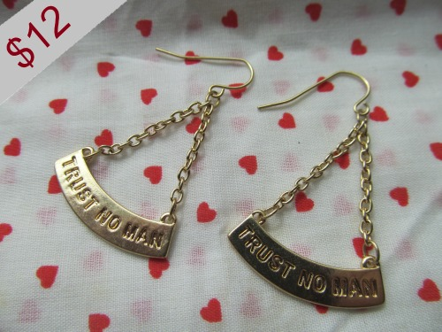 radbreath:  Gold colored miniature Trust No Man banner earrings with inch wide charms for twelve dollars.