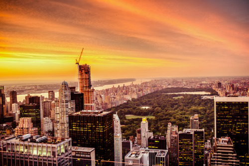 "The New York City Skyline and Central Park from above during sunset.Summer evenings are when the city smolders    as the sun paints the clouds  and the night sky waits just another hour longer  to dance with the last remnants of the day.—-This is a view of the skyscrapers of midtown Manhattan and Central Park from above looking north towards upper Manhattan. I took this at the end of August on a gorgeous, sweltering evening. I made it up to the top deck of Top of the Rock (30 Rock) just as this spectacular sunset was making its way across the sky.    It's hard not to feel overcome with emotion when the summer sky puts on one of its late summer sunset shows. When it happens, the city is bathed in an other-worldly glow as the lights in the buildings twinkle on like stars and the sky and the impossible all seem to melt away into an infinite horizon full of endless possibility.    —-View this photo with a comment thread on my Google Plus page—-Buy ""New York City Skyline and Central Park - Sunset"" Posters and Prints here, email me, or ask for help."