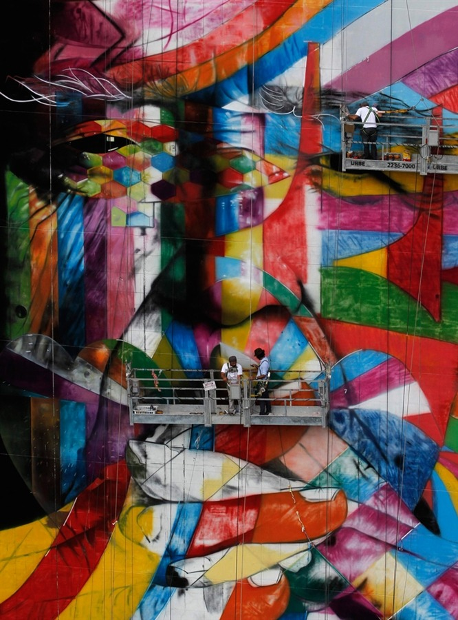 Brazilian graffiti artist Eduardo Kobra (blue shirt) puts the final touches to his piece of art in tribute to Brazilian architect Oscar Niemeyer at the financial center on Sao Paulo's Avenida Paulista, January 22.  Niemeyer, one of the 20th century's most influential modernist architects, died in December 2012 at the age of 104.  (Photo: Nacho Doce / Reuters via NBC News)