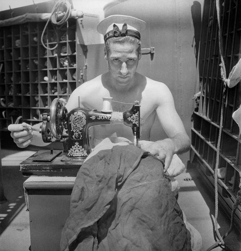 A Royal Navy sailor on board HMS Alcantara uses a portable sewing machine to repair a signal flag during a voyage to Sierra Leone, March 1942 Photograph by Cecil Beaton via Art Blart