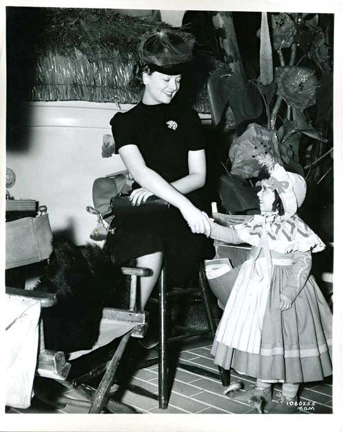 jasonbennion:  Myrna Loy meets a munchkin, presumably on a visit to the set of The Wizard of Oz, 1939.