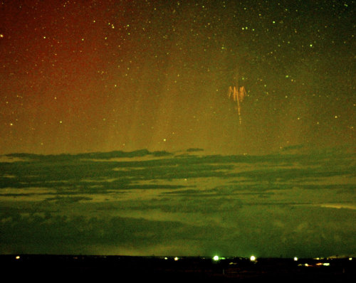 atomstargazer:   APOD | 2013 May 22  |Red Sprite Lightning with Aurora   Image Credit & Copyright:  Walter Lyons (FMA Research), WeatherVideoHD.TV   Explanation:  What's that in the sky? It is a rarely seen form of lightning confirmed only about 25 years ago: a red sprite. Recent research has shown that following a powerful positive cloud-to-ground lightning strike, red sprites may start as 100-meter balls of ionized air that shoot down from about 80-km high at 10 percent the speed of light and are quickly followed by a group of upward streaking ionized balls. The above image, taken a few days ago above central South Dakota, USA, captured a bright red sprite, and is a candidate for the first color image ever recorded of a sprite and aurora together. Distant storm clouds cross the bottom of the image, while streaks of colorful aurora are visible in the background. Red sprites take only a fraction of a second to occur and are best seen when powerful thunderstorms are visible from the side.