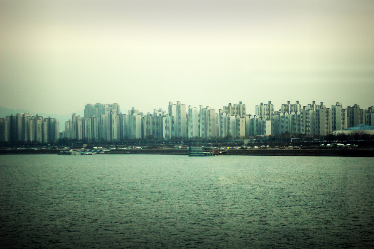 Seoul, looking outside of subway train over Han River. Apartments…