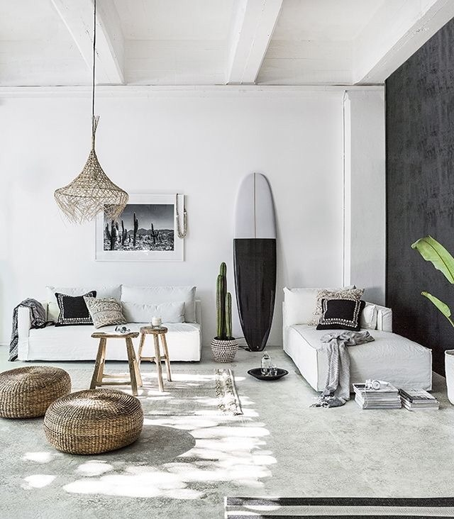 All white decor in a modern bohemian minimal rustic living room with surfboard and natural accents. #allwhitedecor