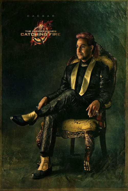 Hunger Games host Caesar Flickerman knows how to rock a pink pompadour and a patterned suit.