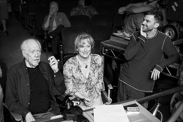 "When Robert Altman made his final film A Prairie Home Companion, a standby director was required as no insurance company would cover the film without one. Paul Thomas Anderson acted as Altman's backup on the set, saying, ""Any hesitation? None. None at all, because I knew he wasn't going to die."" Here he describes Altman's last moments as a director.  The last day we shot the last scene, the one with Kevin with the garbage falling and him playing piano. That was the last thing we shot. And Bob definitely had a melancholy feeling about him, in his face. Because of the way the shot was, we were shooting the whole stage, so Bob was tucked over in Guy Noir's office. Sometimes you get in these horrible places where you just have to be for the shot. And he had a Starbucks coffee in his hand and his coat was zipped up because it was kind of cold in there and he had his glasses on. He was staring at the monitor and he just looked really sad that it was ending. I think we only did the shot twice. I remember sitting there thinking, ""Fuck, do it again, do it… do more, do more."" I wanted to do more — not cause it wasn't good, but I wanted to keep shooting. Oh, I didn't figure on this making me sad. I thought, ""Oh great, I get to talk about Bob."" But it's making me feel like I'm sure everybody feels — they really wish they could call him up. Yeah, fuck! Horrible, sad. He was so indestructible for so long."" —Paul Thomas Anderson on Robert Altman     That would explain the requirement that you have a stand-by director, who turned out to be Paul Thomas Anderson. Paul was very, very generous to do this. It's amazing, I was really surprised. I never would have asked him to do it. He was at my side every moment I was shooting and he was a fantastic help. He never intruded, he never overrode me. I couldn't even say goodbye to him, I would have broken down in tears. Certainly you aware of the homage he's paid to you with films such as ""Boogie Nights"" and ""Magnolia."" He told me he was a big fan of mine. I saw him after ""Boogie Nights"" and he said, ""I just ripped you off."" [chuckles]. —Robert Altman on Paul Thomas Anderson   Paul Thomas Anderson dedicated his 2007 film There Will Be Blood to Altman. PTA on filmmaking:  First part of a series of informative selections from PTA and Philip Baker Hall together. PTA is a known cinephile who comes from the same camp as Quentin Tarantino. A man who had immersed himself in studying cinema by watching a plethora of films and utilized the knowledge gathered from laserdisc commentaries in the late 80′s and early 90′s to learn filmmaking on his own. Of course not many people know he had a leg up in the industry as much as he likes to milk the ""non-film school"" card, but one can still admire the dedication of learning the craft by being a sponge, soaking up all kinds of filmmaking information. —filmschoolthrucommentaries   Previously on Cinephilia and Beyond: Hard Eight (also known as Sydney) screenplay by Paul Thomas Anderson Hard Eight Audio Commentary (1996) with director PT Anderson and actor Phillip Baker Hall Paul Thomas Anderson claims that everything he knows about directing he learned from John Sturges' commentary on the Bad Day at Black Rock LaserDisc Tweet  //  Follow @LaFamiliaFilm  //"