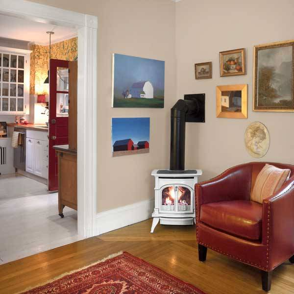 Pantone Sand unifies a salon wall display of the homeowners' Cape Cod barn paintings