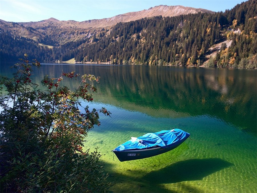 Arnensee Lake, Switzerland  The waters of Arnensee in Switzerland are so clear they cause boats such as the one in the picture to appear as they are hovering in the air.  The lake is located in Canton of Berne in Switzerland, and can be easily reached with a little planning. Although that first picture has made the lake relatively known, it's still usually a quiet, tourist-free place.   Wow, I really want to go here