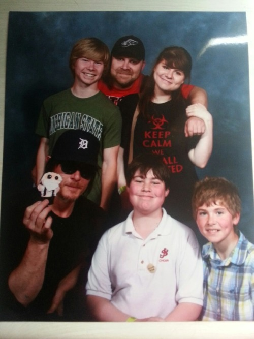 "I almost forgot to post this picture! This is my family & Norman Reedus.  That little doll is supposed to be Hershel. We were really rushed, but he sort of danced in front of us & waved the doll around. He said something but it was kind of loud so we didn't really hear him. He leaned down to get in on the picture, turned to my brothers, smiled proudly as he displayed the doll & said ""Tiny Hershel!""   How fucking adorable, seriously."
