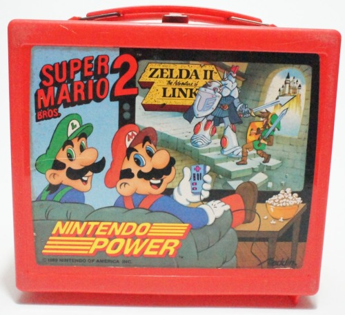 "sharkchunks:  nintendroid:  suppermariobroth:  Mario and Zelda lunchbox.  That's not how you hold an NES controller, Mario.   That's not an NES controller though it looks more like… THEY PREDICTED THE WII REMOTE!!!  I had this lunch box!  Second grade, probably.  It smashed into pieces, so I reverted to my sticker-covered Ghostbusters lunch box.  But before that happened, my friend gave me hell for calling Link ""Zelda.""   That's right, I got Gannon-banned in second grade."