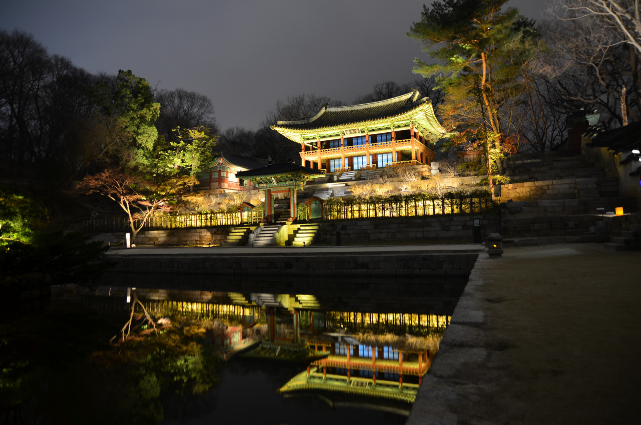 "Changdeokgung Palace (""Prospering Virtue Palace"") was the second royal villa built following the construction of Gyeongbukgung Palace in 1405. The palace gained in importance starting from the time of 9th king of Joseon, Seongjong, when a number of kings began using it as a place of residence. It was the principal palace for many of the Joseon kings and is the most well-preserved of the five remaining royal Joseon palaces.  The palace grounds are comprised of a public palace area, a royal family residence building, and the rear garden which was constructed during the reign of King Taejong. Known as a place of rest for the kings, the rear garden boasts a gigantic tree that is over 300 years old, a small pond, and a pavilion. The garden was kept as natural as possible and was touched by human hands only when absolutely necessary. The most beautiful time to see the garden is during the fall when the autumn foliage is at its peak and the leaves have just started to fall.   It is one of the ""Five Grand Palaces"" built by the kings of the Joseon Dynasty (1392–1897)."
