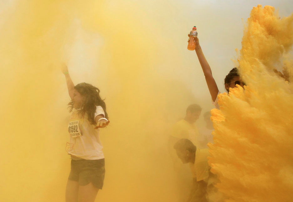 "Participants are hit by colored powder during the ""The Color Run"" in Rio de Janeiro December 16, 2012. The Color Run is a 5 km race where runners are hit with a powder of different colors at each kilometer they pass. REUTERS/Ricardo Moraes"