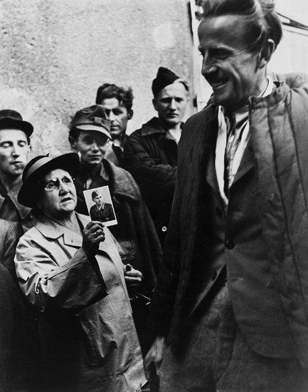 collectivehistory:    Homecoming Prisoners, Vienna, 1947 by Ernst Haas A mother shows a picture of her son to a returning prisoners of war.