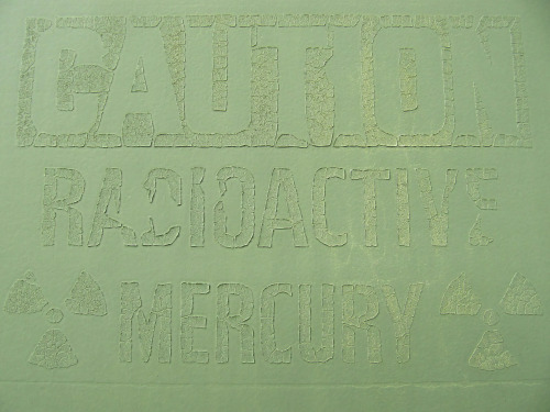 Caution: radioactive mercury (a painted-over warning sign on a well pad in the San Juan Basin, NW New Mexico)