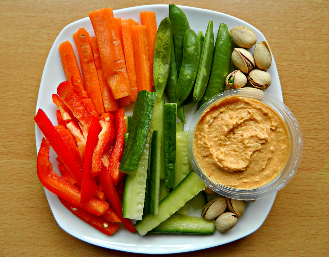 Carrot sticks, sugarsnap peas, red bell pepper, cucumber and red pepper hummus with pistachios.