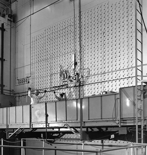 Workers load uranium slugs into the X-10 Graphite Reactor's concrete face. Built as part of the Manhattan Project, X10 was the first-ever production reactor, and acted as a proof of concept for the reactors that would produce materials for the first nuclear bombs, 1943. (Ed Westcott/American Museum of Science and Energy)