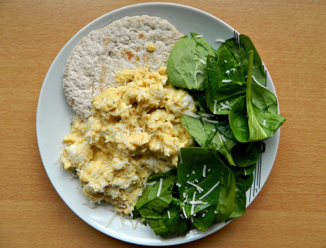 Multi-seed toasted 'Food Doctor' pitta with scrambled eggs, fresh spinach and a light sprinkling of mozzarella. (Eggs - 2 whole, 1 white, dash of soy milk, cumin, basil, black pepper and garlic powder, all cooked in a little coconut oil.)