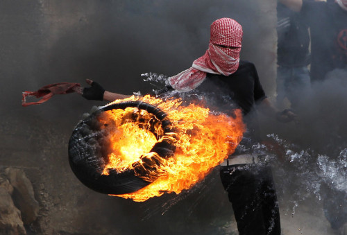 "fotojournalismus:  A Palestinian sets fire to a tyre during clashes between hundreds of Palestinians and Israeli soldiers outside the Ofer prison after a march marking the 65th Nakba day or ""Day of Catastrophe"" on May 15, 2013 in Betunia near the West Bank city of Ramallah. [Credit : Abbas Momani/AFP/Getty Images]"