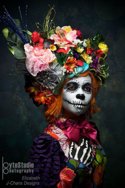 diadelosmuertosmask:  i love how the absolute craziness of color and texture and dimension can do nothing to distract me from the look in her eyes. they speak to me, but i can't understand what she's saying. i'm lost and swimming in her soulful expression, and i wonder for whom she touches her heart… thank you ByteStudio Photography and Elizabeth J-Chans Designs