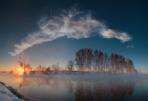 n-a-s-a:  Miass River Sunrise  Image Credit & Copyright: Marat Ahmetvaleev  Miass River Sunrise Image Credit & Copyright: Marat Ahmetvaleev Explanation: Each day on planet Earth can have a serene beginning at sunrise as the sky gently grows bright over a golden eastern horizon. This sunrise panorama seems to show such a moment on the winter morning of February 15. In the mist, a calm, mirror-like stretch of the Miass River flows through the foreground along a frosty landscape near Chelyabinsk, Russia. But the long cloud wafting through the blue sky above is the evolving persistent train of the Chelyabinsk Meteor. The vapor trail was left by the space rock that exploded over the city only 18 minutes earlier, causing extensive damage and injuring over 1,000 people. A well-documented event, the numerous webcam and dashcam video captures from the region soon contributed to a reconstruction of the meteor's trajectory and an initial orbit determination. Preliminary findings indicate the parent meteoriod belonged to the Apollo class of Earth crossing asteroids.