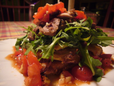 Warm salad of duck confit and arugula served on gratins deauphinois with a grape tomatos salsa and garlic flowers.