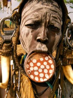 megan-roome:  Photograph from Ian Transue, National Geographic A Mursi woman from the Omo Valley in southern Ethiopia is adorned with face markings and an ornamental clay lip plate, considered signs of beauty among her people.